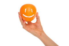 Hand holds orange with drawn smile Stock Photo