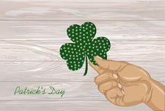 Hand holds ornate clover four-leaf. Celebration concept St. Patr Royalty Free Stock Images
