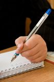 The hand holds a pen. The hand of the boy holds a pen. On a table the notebook lies Royalty Free Stock Images