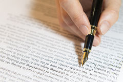 Hand holds pen over the text Stock Photos