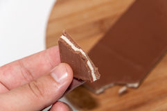 Hand holds piece of chocolate Stock Photography