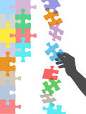 Hand holds piece to solve falling puzzle Royalty Free Stock Photos