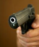 The hand holds a pistol. The person directs a pistol on the purpose Stock Images