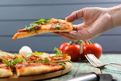 Hand holds pizza slice. Thin pizza with rocket salad and tomatoe. S on background closeup Royalty Free Stock Photography