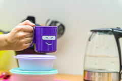 Hand holds plastic cup with smiling face. Close up hand holding bright violet tea mug with a funny face on it Royalty Free Stock Images