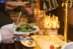 Hand holds plate of food. Hand holds plate with shrimp in cream in snifter and arugula salad Stock Photography