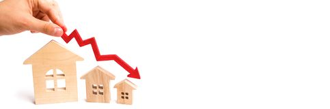 The hand holds a red arrow above the wooden houses down. The houses are decreasing. The concept of falling demand and supply in th stock photo
