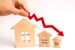 The hand holds a red arrow above the wooden houses down. The houses are decreasing. The concept of falling demand and supply in th stock image