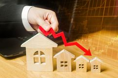 The hand holds a red arrow above the wooden houses down. The houses are decreasing. The concept of falling demand and supply in t stock image