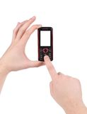 Hand holds red-black cell phone. Royalty Free Stock Images