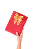 Hand holds red box with gold bow studded asterisks Royalty Free Stock Photography