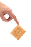 Hand holds saltine soda cracker. Royalty Free Stock Photo