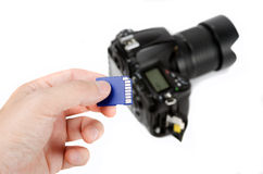 Hand holds SD Memory card with DSLR camera on the background Stock Photography