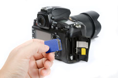 Hand holds SD Memory card with DSLR camera on the background Stock Images