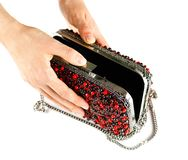 Hand holds a small red female purse covered with stones. Clutch royalty free stock photos