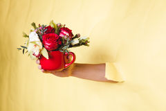 Hand holds small vase with flowers and rose breakes through a yellow background Stock Photography