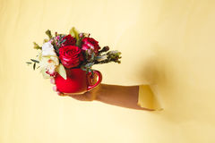 Hand holds small vase with flowers and rose breakes through a yellow background Royalty Free Stock Images