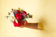 Hand holds small vase with flowers and rose breakes through a yellow background Royalty Free Stock Photo