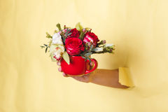 Hand holds small vase with flowers and rose breakes through a yellow background Royalty Free Stock Photos