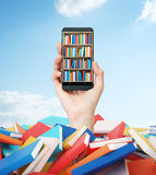 A hand holds a smartphone with a book shelf on the screen. A heap of colourful books. A concept of education and technology.Cloudy. Blue sky on the background royalty free stock photography