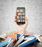 A hand holds a smartphone with a book shelf on the screen. A heap of colourful books. A concept of education and technology. Stock Photography