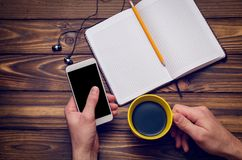 A hand holds a smartphone and a cup of coffee over a wooden table with a notebook royalty free stock photo