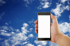 Hand holds smartphone with sky on background Royalty Free Stock Image