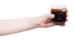 Hand holds soft drink with ice in glass Royalty Free Stock Photography