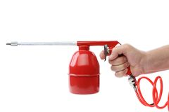 Hand holds spray gun with plastic spring. Royalty Free Stock Photos