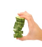 Hand holds stack of sliced cucumber. Royalty Free Stock Image