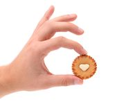 Hand holds sweet pastry with white cream heart. Stock Photos