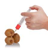 Hand holds the syringe on kiwi Royalty Free Stock Images