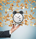 A hand holds a tablet with alarm clock. Golden coins are falling down from the ceiling. The concept of time is money. Light blue b Stock Photography