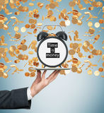 A hand holds a tablet with alarm clock. Golden coins are falling down from the ceiling. The concept of time is money. Light blue b Stock Photos