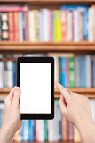 Hand holds tablet pc and bookcase Royalty Free Stock Photo