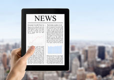Hand Holds Tablet PC With News. Man hands are holding touch screen device with news. Blurred cityscape with skyscrapers on background Royalty Free Stock Images