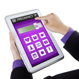 Hand holds tablet with pregnancy app Stock Photos