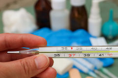 Hand holds thermometer. Body temperature of 38.4 C Royalty Free Stock Photos