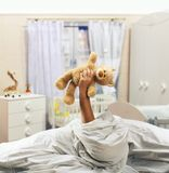 Hand holds toy bear above the bed Royalty Free Stock Image