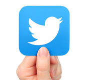 Hand holds Twitter icon on white background Stock Photos