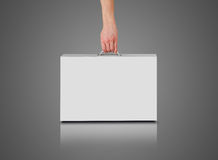 Hand holds a white box with a handle. Packing box for laptop. Stands on a reflection floor. Isolated on grey background Stock Photo