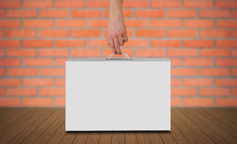 Hand holds a white box with a handle. Packing box for laptop. Stands on a wooden floor. On red brick wall background Stock Photo