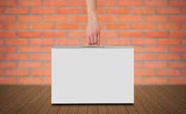 Hand holds a white box with a handle. Packing box for laptop. Stands on a wooden floor. On red brick wall background Stock Images