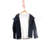 Hand holds a white t-shirt and black jacket  on a hanger on a wh Royalty Free Stock Image