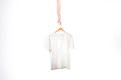 Hand holds a white t-shirt on a hanger on a white background. Hand holds a white t-shirt on a hanger on a white Royalty Free Stock Images