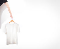 Hand holds a white t-shirt on a hanger on a white background. Hand holds a white t-shirt on a hanger on a white Stock Photos