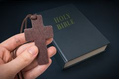 Hand holds wooden cross above Holy Bible Royalty Free Stock Photos