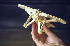 Hand holds Wooden toy plane that flies on a dark background in retro style Stock Photography