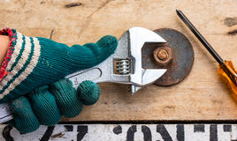 Hand holds wrench and tighten the nut on the wooden Royalty Free Stock Photography