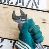 Hand holds wrench and tighten the nut on the wooden Stock Photos